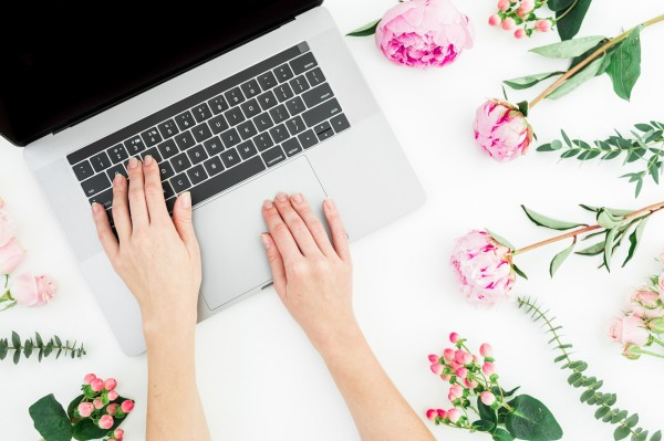 Woman typing on laptop. Office workspace with female hands, laptop, notebook and pink flowers on white background. Top view. Flat lay.