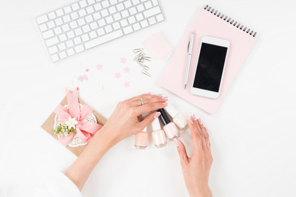 female hands with beautiful manicure holding nail polishes at workplace